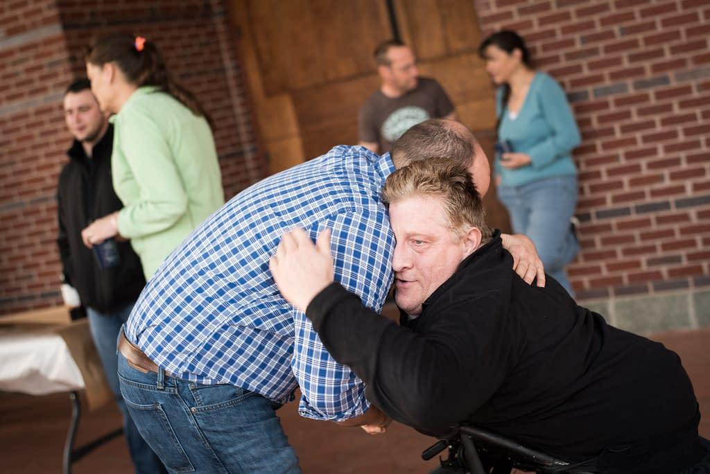 Decorative Image - Man hugging man in wheelchair